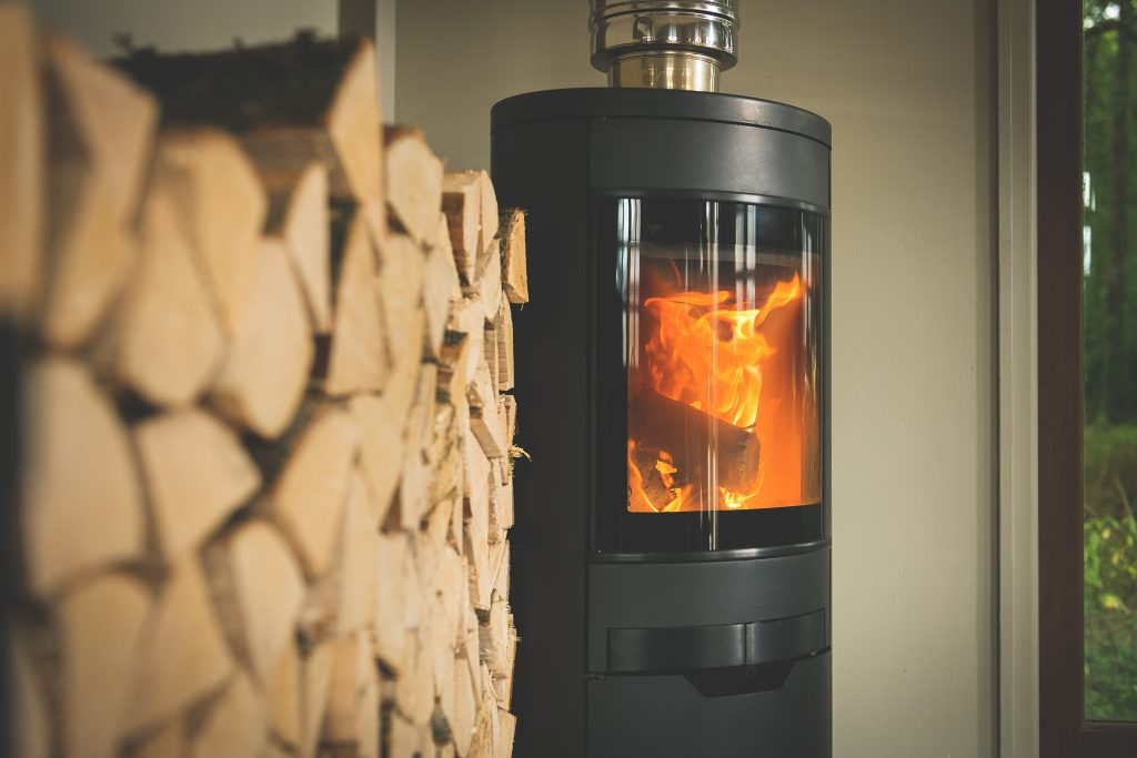 A fire rages in a log burner next to a stack of kiln-dried logs