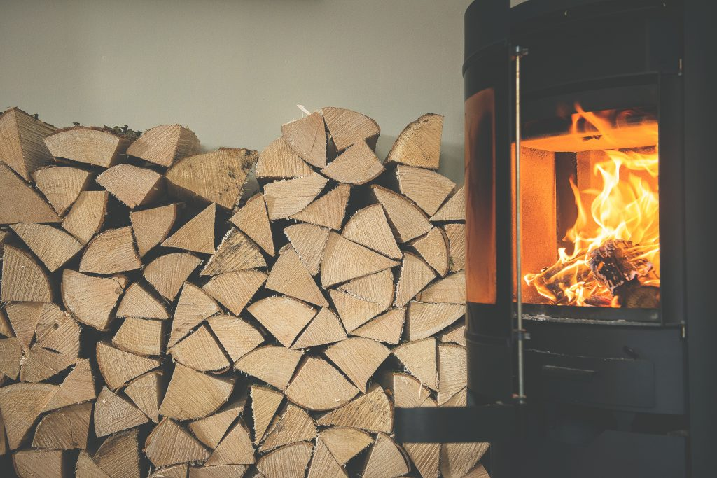 A log burner with an open door next to a stack of Cornish kiln-dried firewood