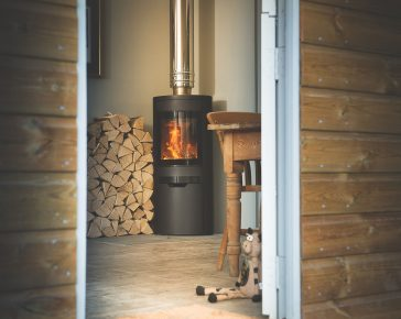 A log burner next to a pile of firewood heats a small home