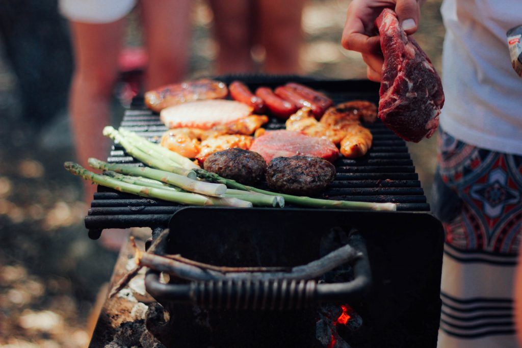 A person cooks assorted meats and vegetables over a wood-fired grill