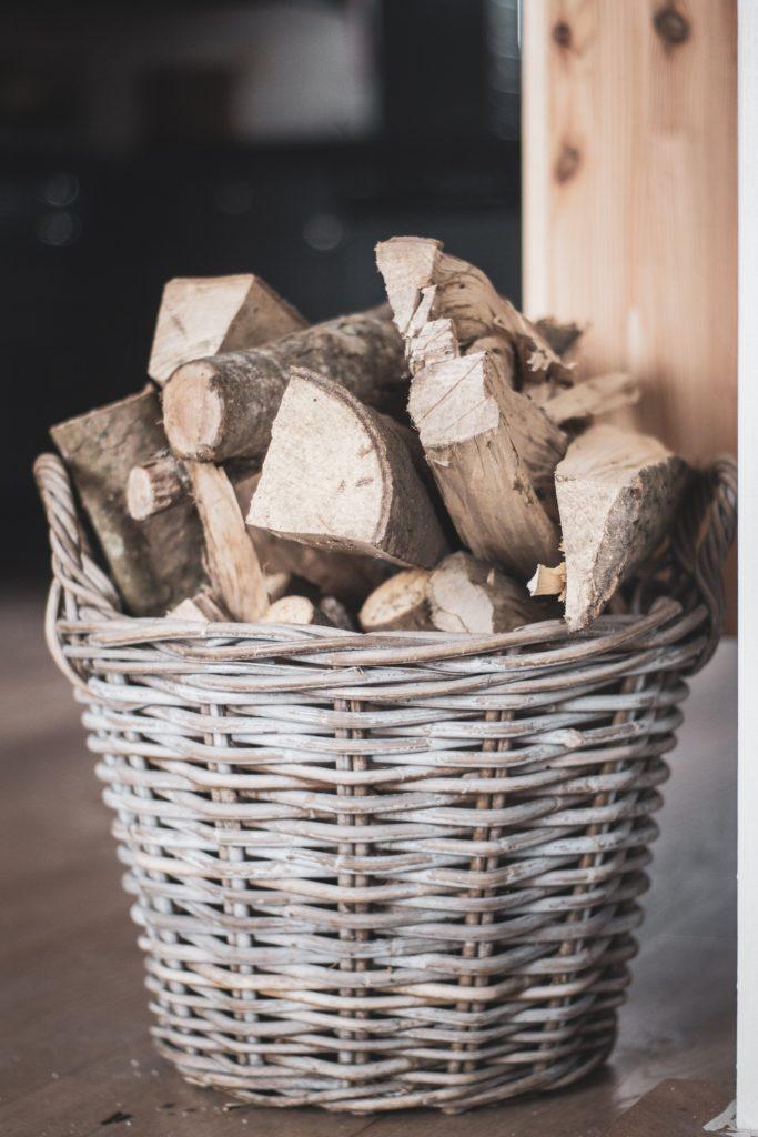 A wicker basket full of firewood logs